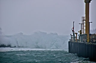 Waves crash over the jetty during a storm.